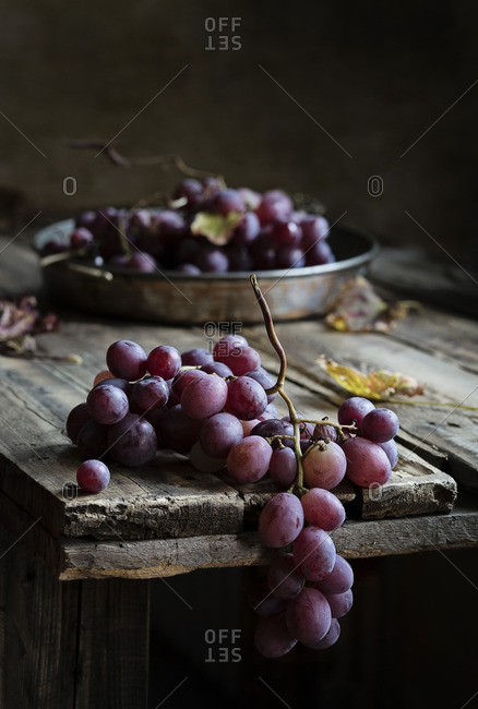 Bunch of red grapes on the edge of a rustic wooden table