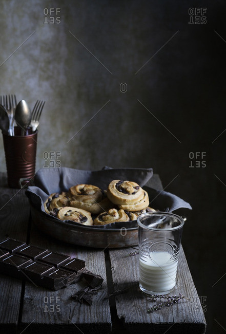 Homemade cinnamon rolls and glass of milk on a rustic table