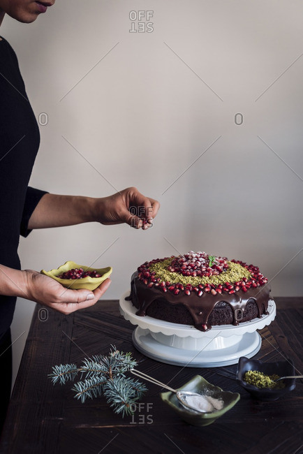 Woman decorating a chocolate Christmas cake with pomegranate seeds