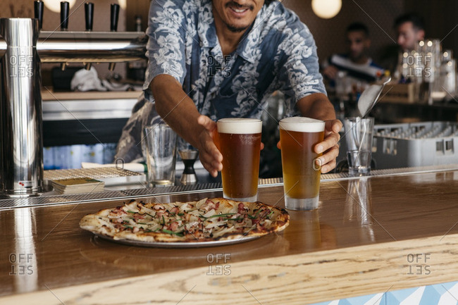 Man serving beer and pizza at bar