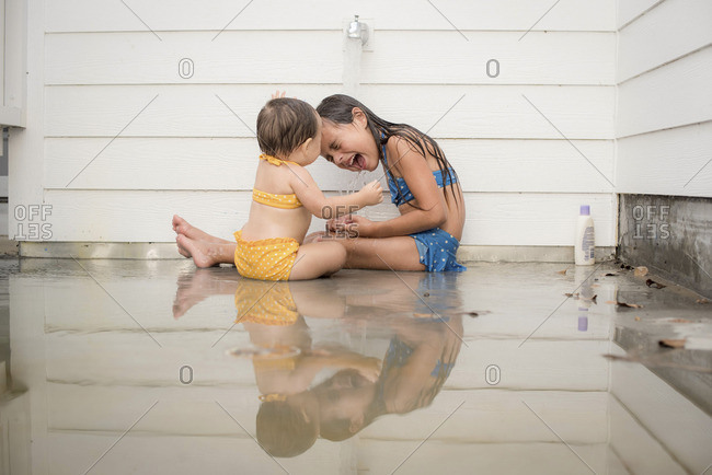 Girls laughing by an outside faucet
