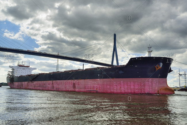 Container ship on the river Elbe beneath the Koehlbrandbruecke bridge, river Elbe, Hamburg, Germany