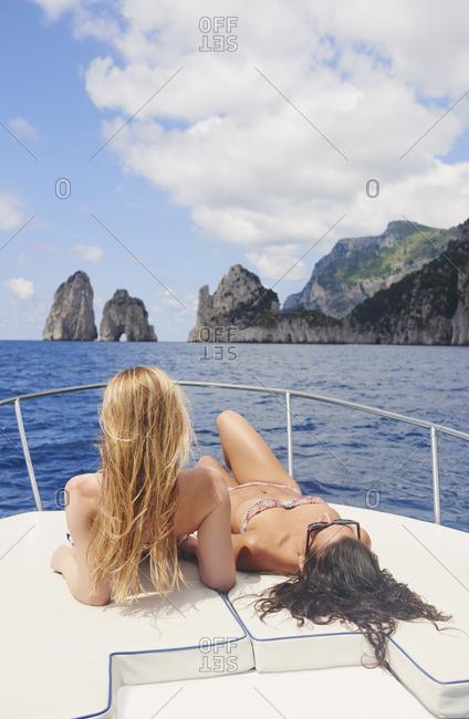Women sunbathing on speedboat