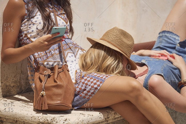 Women lounging with phone on stone bench