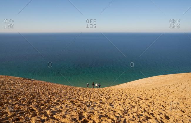 Two couples walking down sandy hill at Sleeping Bear Dunes National Lakeshore, Michigan