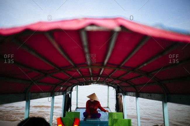 A woman pilots a boat through the floating market in Chau Doc in the Mekong Delta, in southern Vietnam
