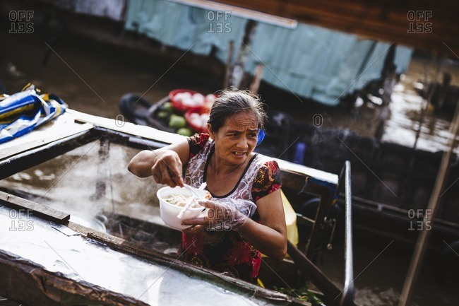 Can Tho, Vietnam - October 3, 2016: A woman selling Hu Tieu noodles from her boat at the Cai Rang floating market in the Mekong Delta in southern Vietnam