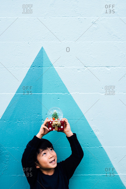 Little boy holding snow globe in the air
