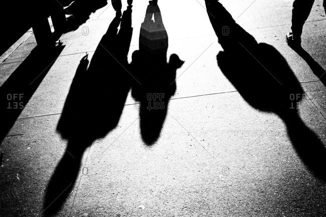 Shadows of people on city sidewalk