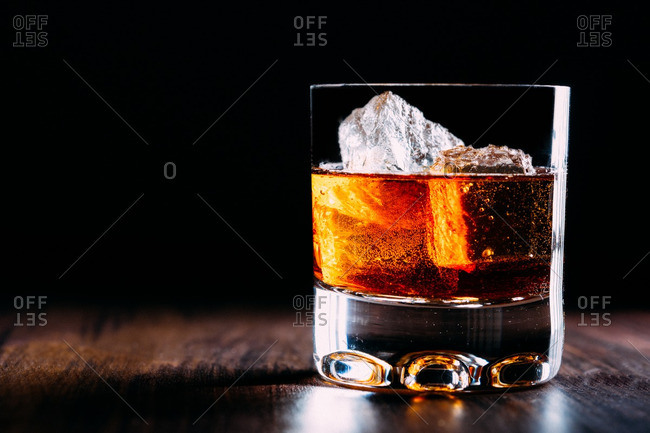 Glass of whiskey on a wooden table and dark background
