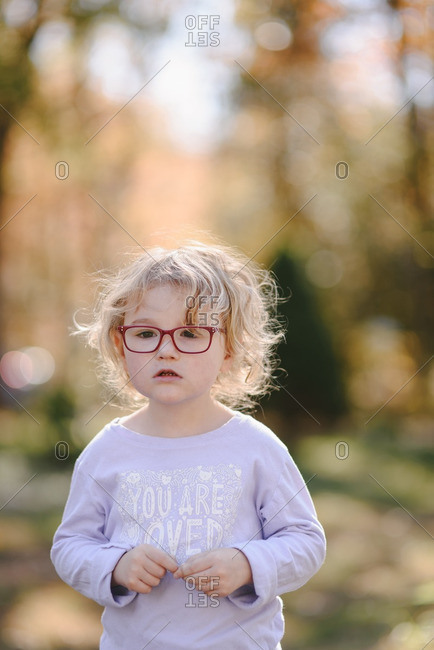 Little blonde girl with glasses standing outdoors