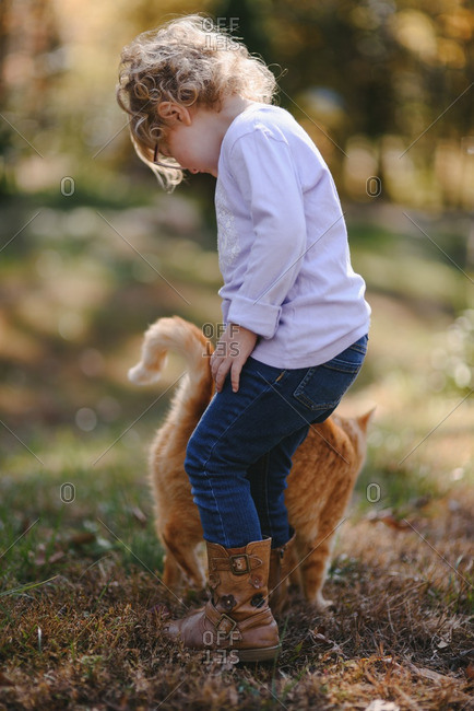 Little blonde girl petting an orange cat outdoors