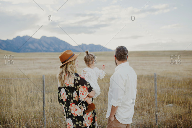 Mother holding her daughter who is pointing into the vast countryside