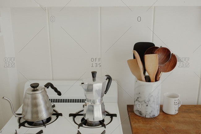 Vintage tea kettle and coffee pot on stovetop next to container of kitchen utensils