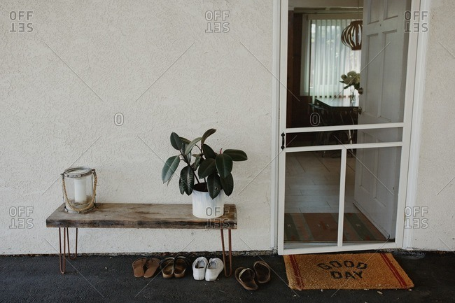 Entrance to home with screen door, welcome mat, and a small table with decorations