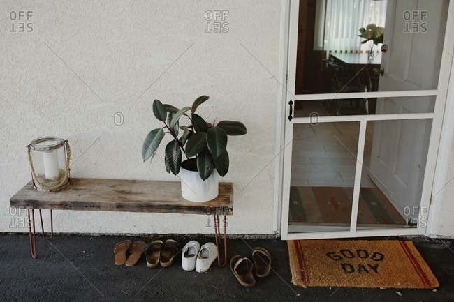 Entrance to house with screen door, welcome mat, and a small table with potted plant