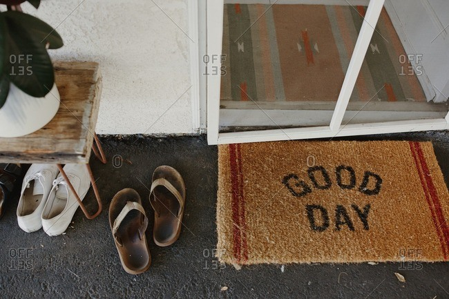 Doormat and shoes removed outside front door of house