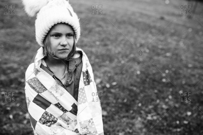 Portrait of young girl wearing a winter hat and wrapped in quilt