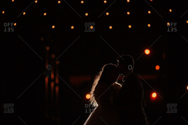 Silhouetted groom kissing bride beneath twinkling lights