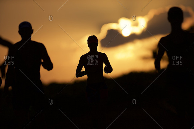 Silhouetted triathletes running at sunset