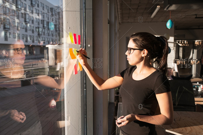 Woman writing on sticky notes on window
