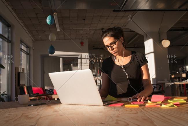 Woman in open office on her laptop