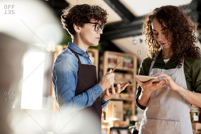 Running small business. Two curly concentrated female entrepreneurs in aprons working in their store