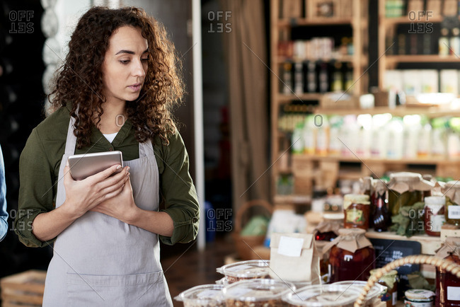 Portrait of curly concentrated female entrepreneur in apron running a small store with homemade products