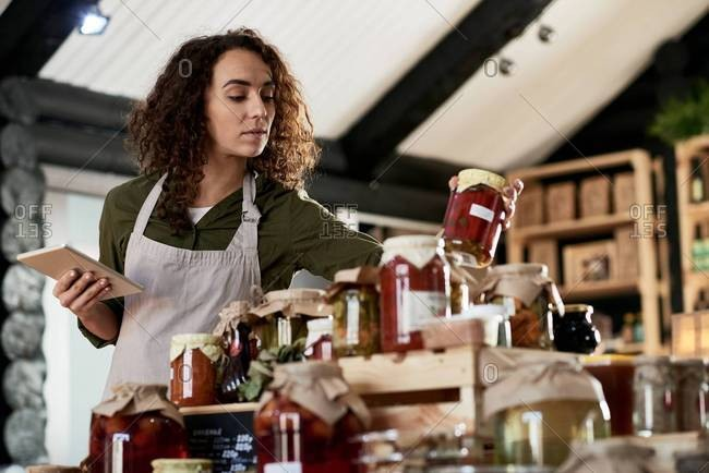 Beautiful curly shop assistant in apron working in small store with organic goods