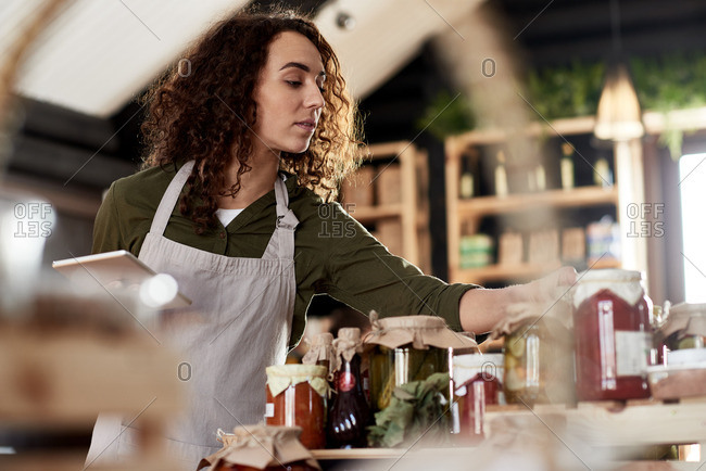 Low angle view of concentrated curly female entrepreneur in apron working in organic food store