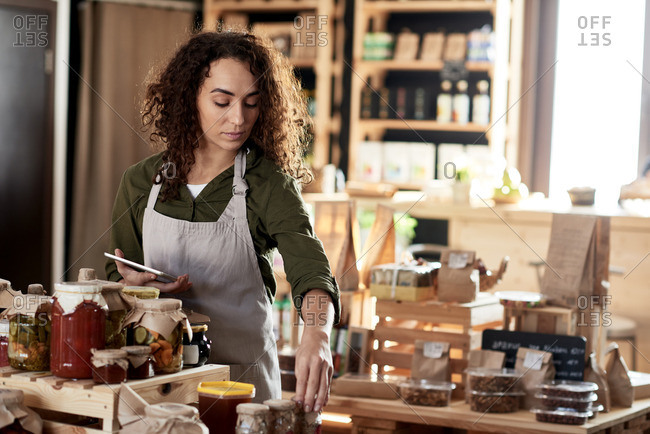 Portrait of young curly businesswoman in apron running a small organic food store
