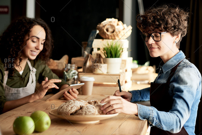 Two creative female entrepreneurs in aprons running a small shop with organic food