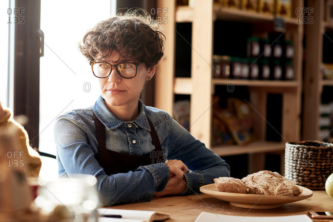 Portrait of pensive sales associate with short haircut working at natural products store