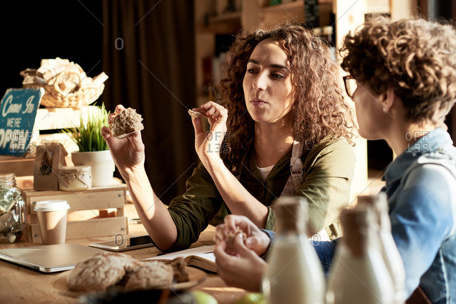 Enjoying homemade food. Two young curly shop assistants working in a small shop with bio products
