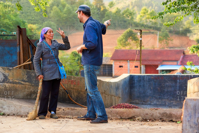 Menglian, Yunnan, China - February 29, 2016: Workers talking on a coffee farm
