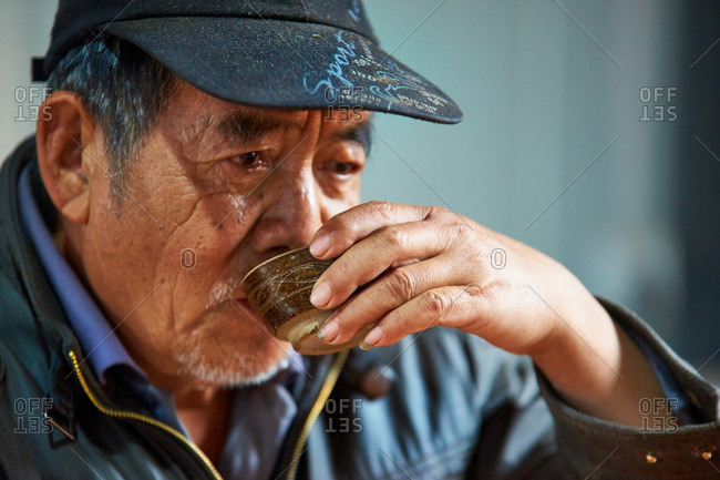 Menglian, Yunnan, China - March 1, 2016: Chinese man drinking tea