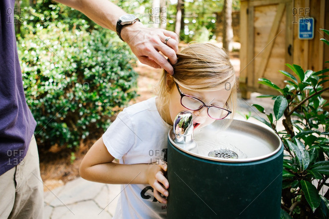 Father pulling hair back while his daughter drinks from a water fountain