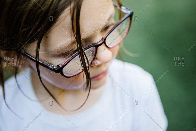 Little girl with wet hair and water droplets on her glasses