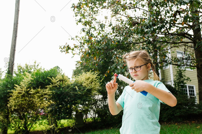 Little girl playing with a finger rocket