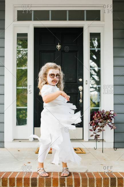 Girl twirling her ghost costume on Halloween on front porch
