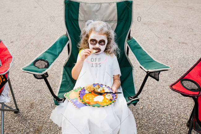 Girl dressed as a ghost eating a snack on Halloween