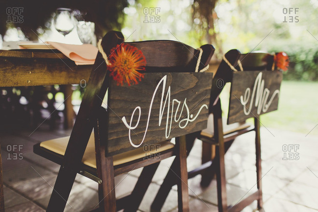Mr. and Mrs. signs hanging from wooden chairs