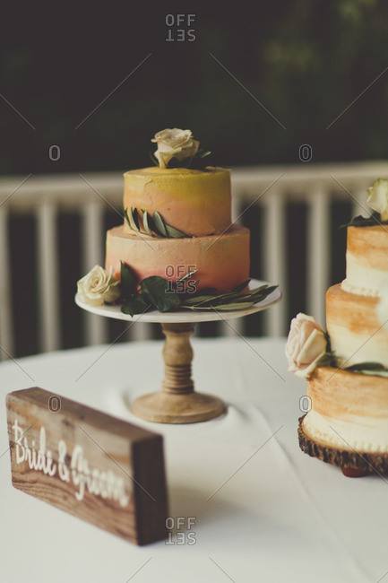 Mr. and Mrs. sign by cakes at a wedding