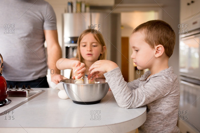 Children cracking eggs into a bowl