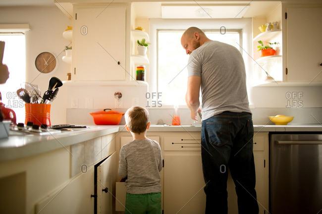 Little boy helping dad wash dishes