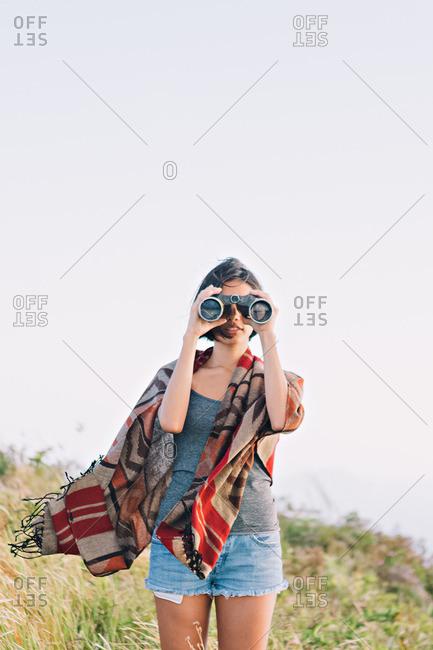 Woman in country looking through binoculars