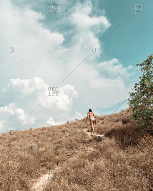 Woman walking up hill in bikini