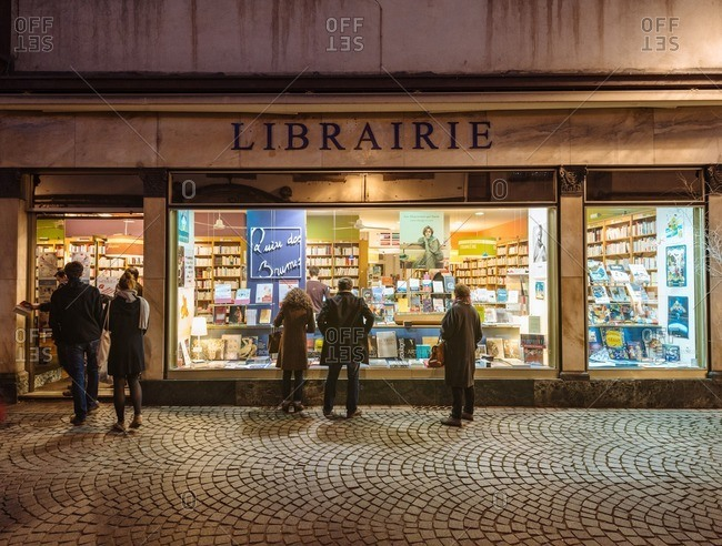 Strasbourg, France - December 6, 2015: People looking in the windows of a book shop on the cobbled and iconic Grand Rue in old city center