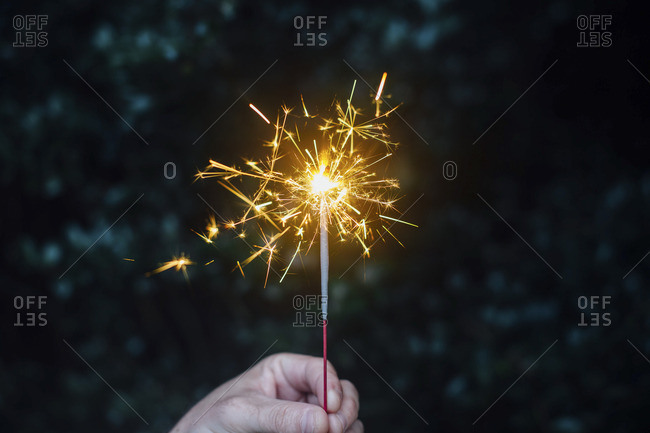 Hand holding up a sparkler