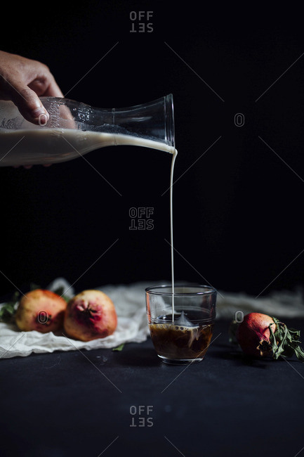 Pouring cream into coffee glass